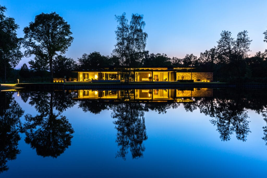 view of lakeside villa at night from the lake